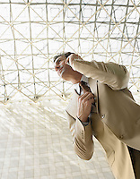 Businessman using mobile phone outdoors (low angle view)