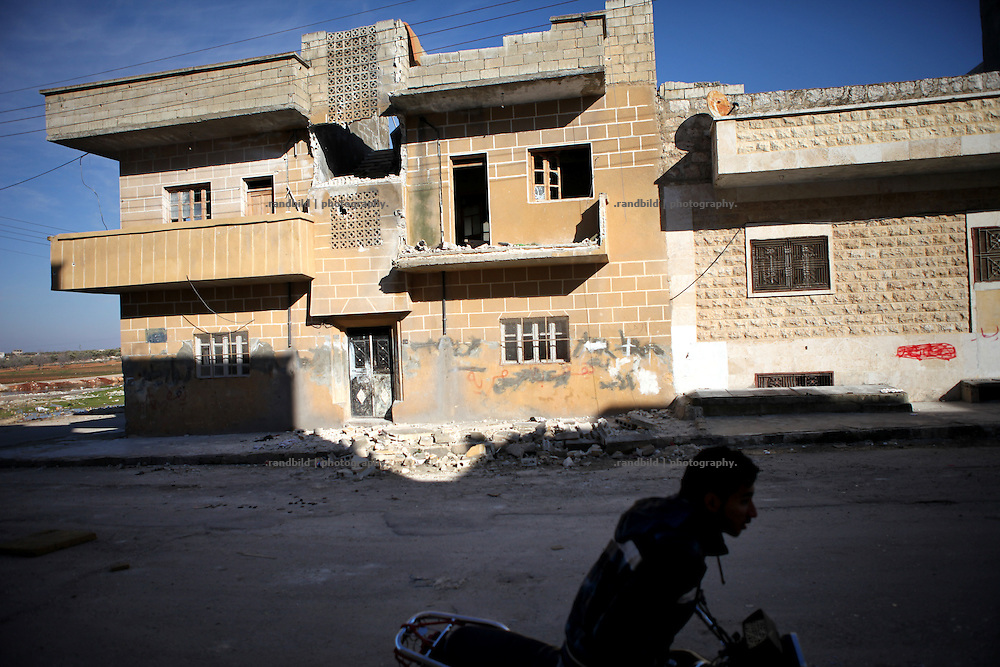 A man on a motorcycle drives along a shelled residential house in the outskirts of Idlib, Province of Idlib, Syria.