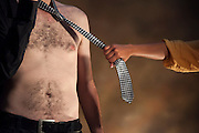 Womans hand pulls shirtless man by his tie