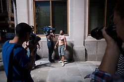 © London News Pictures. 04/09/2013. London, UK. The media film nd photograph a man sunbathing topless in the suns light as it reflects off 20 Finchurch Street in the financial district of central London. The building, which has been named unofficially the 'Walkie Talkie' building because of its shape, intensifies the suns light and reflects it onto the street below. There have been reports of damage to vehicles and local shops caused by the heat of the reflected light. Photo credit: Ben Cawthra/LNP