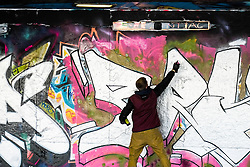 Graffiti artists decorating a wall in Leake Street in Waterloo. London