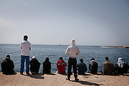 ITALY. Lampedusa:Tunisian migrants wait the arrival of boats at Lampedusa on March 26, 2011.  Copyright Christian Minelli.
