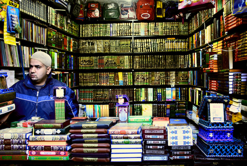 Niche bookshop crammed with newly bound Islamic books for students at the university in the Fez Medina.  View over the counter stacked with more books and Korans.  Male bookseller wearing a close cap looks determinedly off to the left.