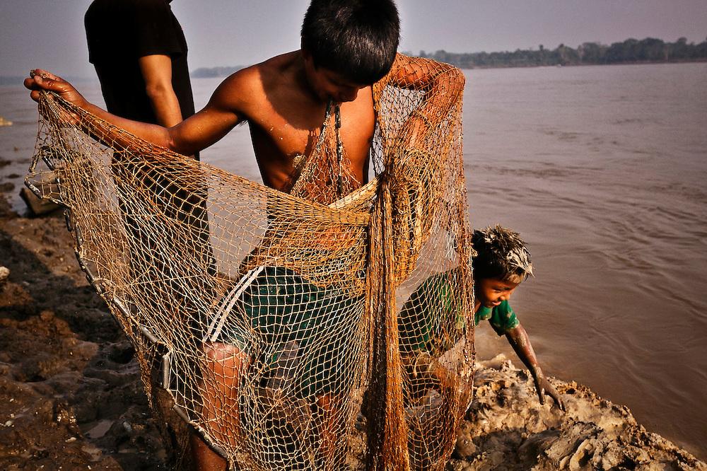 Colombia, Mocagua, 2010. Cazando vida. <br /> La pesca es pilar fundamental de la vida cotidiana y la econom&iacute;a en Amazonas. Especies como el piraruc&uacute;, el pez de agua dulce m&aacute;s grande conocido, y hasta mam&iacute;feros habitan estas aguas tibias. En el lago Tarapoto viven los delfines rosados, &uacute;nicos en el mundo y que solo se reproducen y pueden verse en este r&iacute;o. Los ni&ntilde;os aprenden el arte de la pesca de sus padres y abuelos, entre los juegos y la esperanza de cazar la mejor presa.  <br /> Hunting life. <br /> Fishing is a fundamental part of daily life and the economy in Amazon. Species like the piraruc&uacute;, the largest fresh water fish, and mammals inhabit these warm  waters. In Lake Tarapoto live pink dolphins which are unique to this part of the world and only breed and can be seen in this river. Children learn the art of the fishing from their parents and grandparents, between their games and the hope to hunt the best prey.