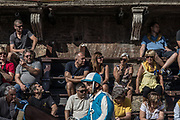 "Italy, Siena, the Palio: Carlo Sanna , socalled Brigante, Onda.  preparing for the  trial called "" Provaccia"" , the bad trial, for the lack of enthuasiasm shown by the jockeys who spare the horses for the demanding evening race. If you want to see the Palio you can choose among the wooden Seats called ""Palchi"" (all around the square), the windows of the Palaces on the Square and the balconies. The last are very few and, as they have a higher position and better view, like the windows,  they are more expensive. The balconies can accommodate up 2 rows of people (the first have chairs the second just stand). The windows are managed directly by the owners of the Palaces in the Campo Square or by the same Palio Business Men. After this test, captains and jockeys gather at the City Hall to enscribe the jockey and show his colors. After this the jockey can no longer be changed."