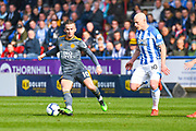 James Maddison of Leicester City (10) and Aaron Mooy of Huddersfield Town (10) in action during the Premier League match between Huddersfield Town and Leicester City at the John Smiths Stadium, Huddersfield, England on 6 April 2019.