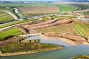 Nederland, Noord-Brabant, Werkendam, 28-10-2014; Ruimte voor de Rivier project Ontpoldering Noordwaard. Overzicht richting Nieuwe Merwede. Langs de rivier de bestaande bandijk met betonnen doorlaten annex bruggen. In de voorgrond grondwerk t.b.v. de aanleg van meanderende kreken, inclusief nieuwe brug.<br /> De Noordwaard wordt ontpolderd door de dijken aan de rivierzijde gedeeltelijk af te graven, hierdoor kan derivier bij hoogwater via de Noordwaard sneller naar zee stromen. Gevolg van de ingrepen is ook dat de waterstand verder stroomopwaarts zal dalen.<br /> National Project Ruimte voor de Rivier (Room for the River) By lowering and / or moving the dike of the Noordwaard polder the area will become subject to controlled inundation and function as a dedicated water detention district. Houses and farmhouses will be constructed on new dwelling mounds. <br /> luchtfoto (toeslag op standard tarieven);<br /> aerial photo (additional fee required);<br /> copyright foto/photo Siebe Swart