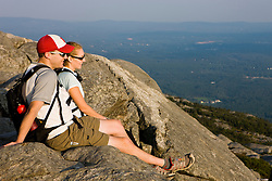 A couple rests on the summit of Mount Monadnock in Monadnock State Park in Jaffrey, New Hampshire.