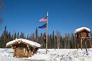 Amerkanska flaggan och Alaskas delstatsflagga tillsammans med timmerhus. <br /> Alaska, USA