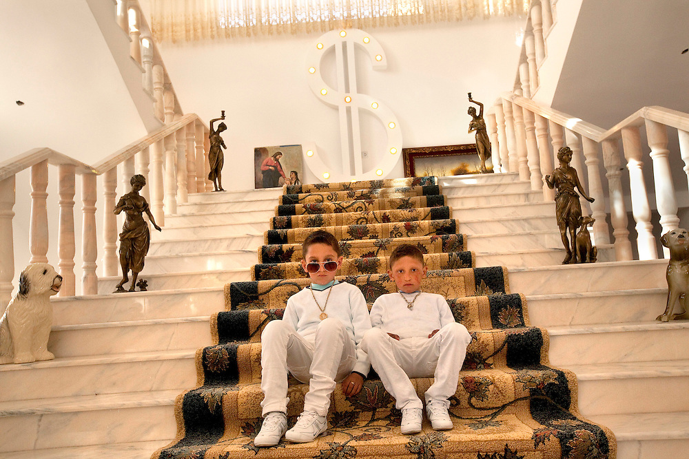 Six-year old twins Gelu and Edi Petrache sit on stairs in a mansion on Easter Sunday in Buzescu, a small town in Romania.