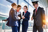 Portrait of mature pilot talking with young attractive flight attendants during arrival in airport