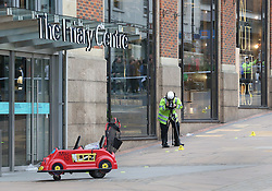 © Licensed to London News Pictures. 23/10/2015. Guilford, UK. . A child's shopping buggy (L)  is visible by the entrance to The Friary shopping centre after a car injured a number of pedestrians.  Photo credit: Peter Macdiarmid/LNP