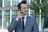 Happy businessman conversing on cell phone outside office