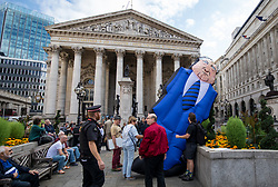 © Licensed to London News Pictures. 15/09/2018. London, UK. Demonstrators erect an inflatable banker at a rally outside The Royal Exchange in the City of London to mark the 10th anniversary of the financial crisis. Photo credit: Rob Pinney/LNP