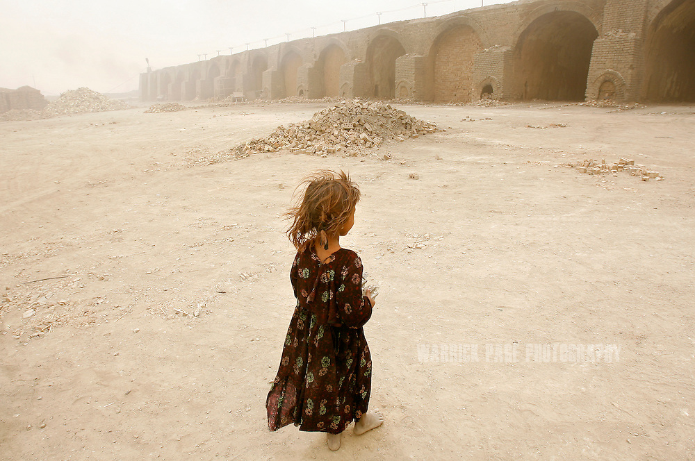 IRAQ, NARWAN - JULY 1: A bare-foot young girl looks out at one of the kilns at the Narwan brick factory, July 1, 2008 in Narwan, Iraq. Twenty miles east of Baghdad, the 170+ small brick factories employ about 30,000 Iraqis, shaping mud into bricks and fire them in kilns burning heavy fuel oil that produces acrid, black smoke visible from satellite imagery 50 miles above the earth's surface. The brick factory employs seasonal workers, many of whom are children - some are as young as four - in highly toxic conditions offering minimal food and water. Respiratory problems are common amongst the workers and children, with no medical personal available to treat them. (Photo by Warrick Page)