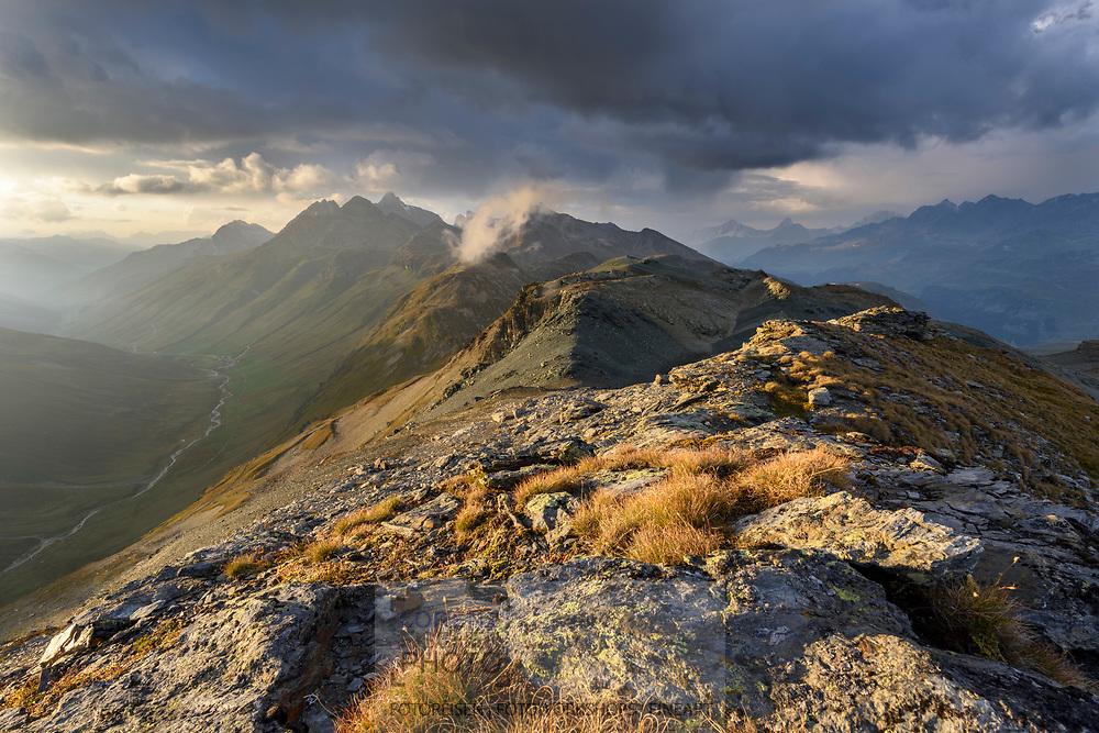 Streiflicht am Abend auf einem Bergr&uuml;cken oberhald der Forcellina. Links unten liegt das Avers Tal mit Juf. Juf gilt als die h&ouml;chstgelegene ganzj&auml;hrig bewohnte Siedlung der Schweiz und eine der h&ouml;chstgelegenen Europas. Im Hintergrund die Oberhalbsteiner Alpen mit dem Phiz Platta, Bivio, Parc Ela, Graub&uuml;nden, Schweiz<br /> <br /> Last side light of the evening on a ridge above the Forcellina. To the left lies the valley Val Avers with the hamlet Juf, in the background the Oberhalbsteiner alps with the Piz Platta, Bivio, Parc Ela, Grisons, Switzerland