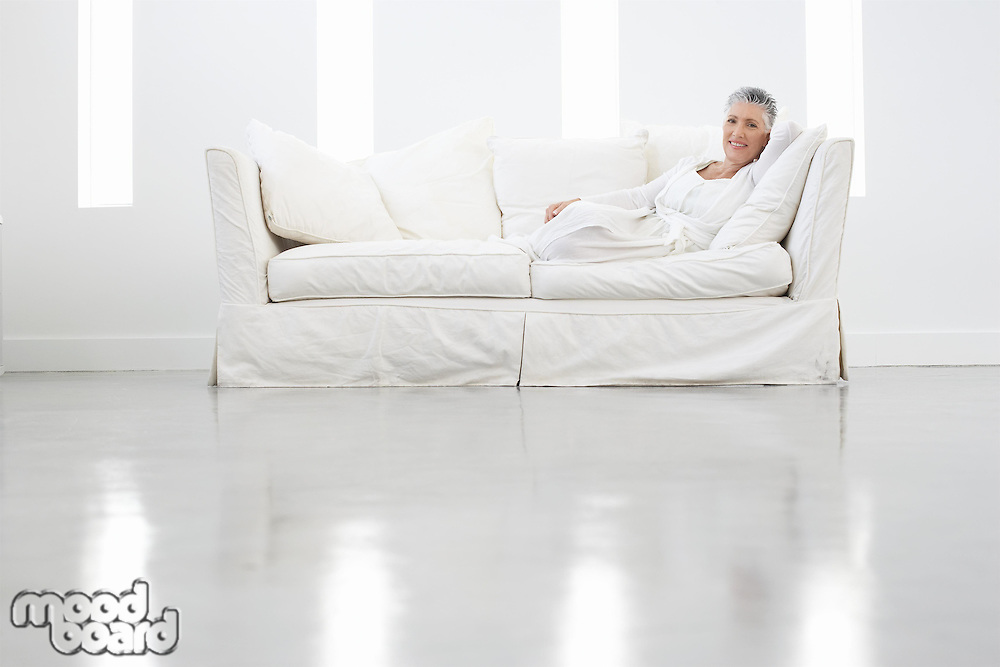 Woman Relaxing on White Sofa