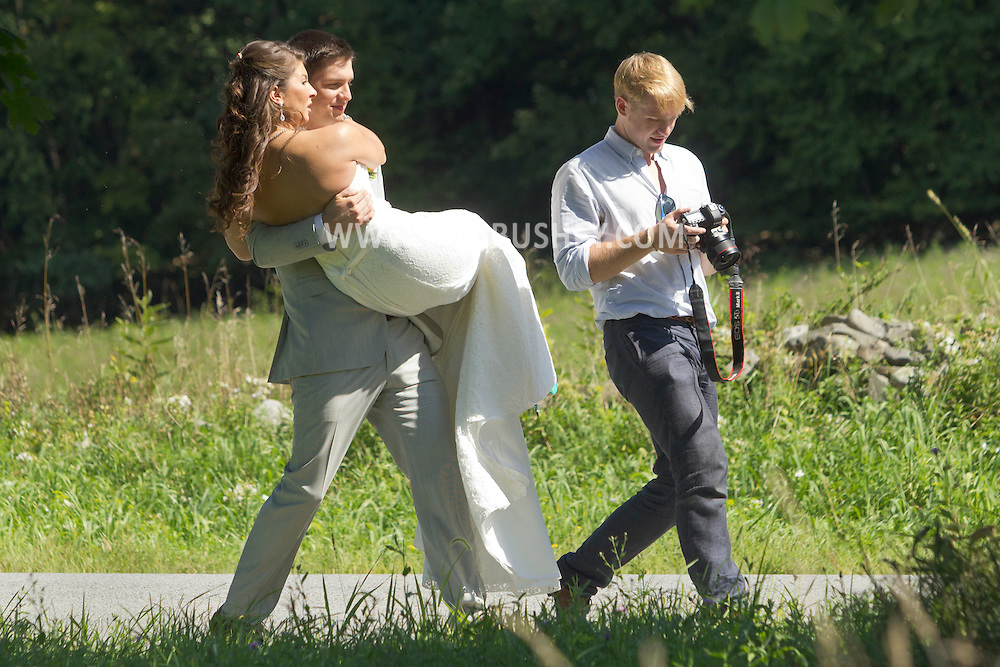 Salisbury Mills, New York - A professional photographer takes pictures of a bride and groom and their wedding party in a grassy field by the Moodna Viaducts on Aug. 26, 2012.