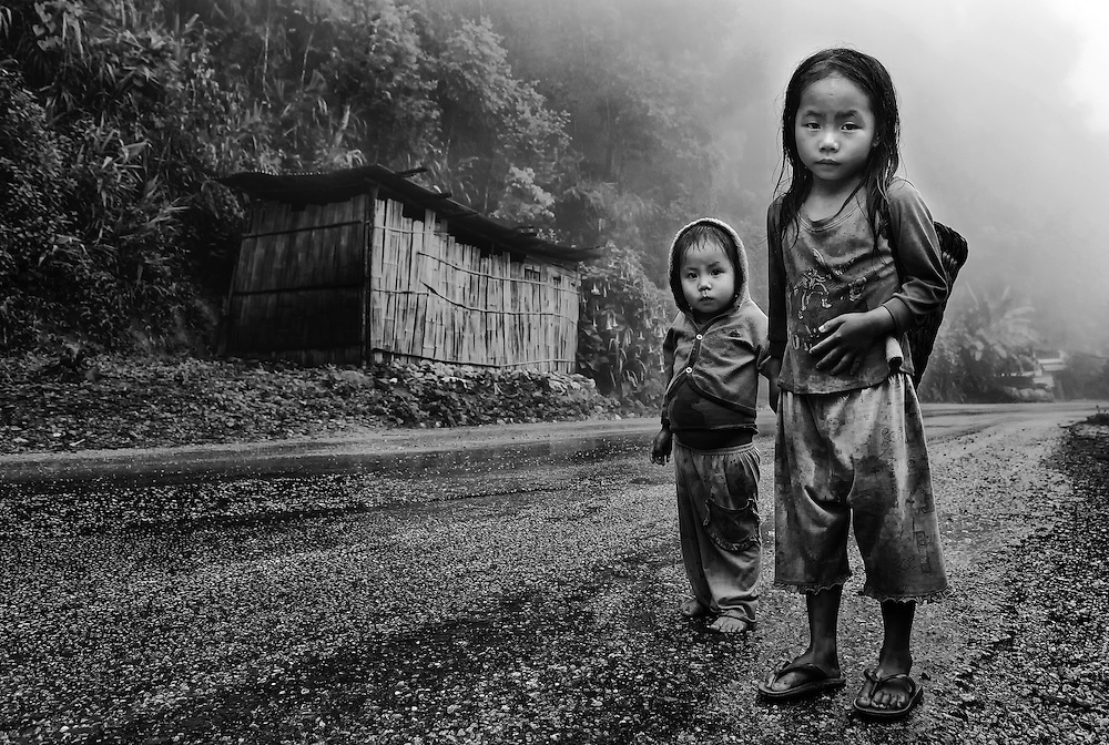Children in the mist and rain near their village in the mountains near Luang Prabang, Laos.<br />