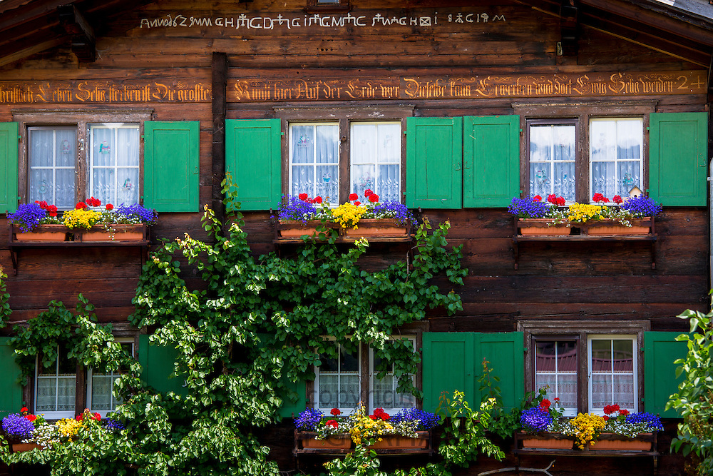 Typical Swiss wooden Alpine chalet style house with inscription in Klosters in Graubunden region, Switzerland