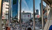 As seen from Starbucks, Shibuya Crossing in Tokyo is the world's single busiest pedestrian crossing, about 2500 people at a time. The intersection is heavily decorated by neon advertisements and giant video screens. What makes Shibuya Crossing so busy is Hachiko Exit of Shibuya Station. Shibuya Station hosts a major hub for shinkansen (bullet trains) and the beginning and end of two subways. Shibuya Station handles about 2 million people daily, the third busiest transportation hub in Tokyo. Shibuya is one of 23 city wards in Tokyo, but often refers to just the popular shopping and entertainment area found around Shibuya Station. Shibuya is a center for youth fashion and culture, the birthplace to many of Japan's fashion and entertainment trends.  The Tokyo urban area is home to over 38 million people. This image was stitched from multiple overlapping photos.
