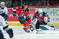 KELOWNA, BC - NOVEMBER 20: Roman Basran #30 keeps his eye on the puck as Liam Kindree #26 of the Kelowna Rockets takes control and clears the zone against the Victoria Royals at Prospera Place on November 20, 2019 in Kelowna, Canada. (Photo by Marissa Baecker/Shoot the Breeze)