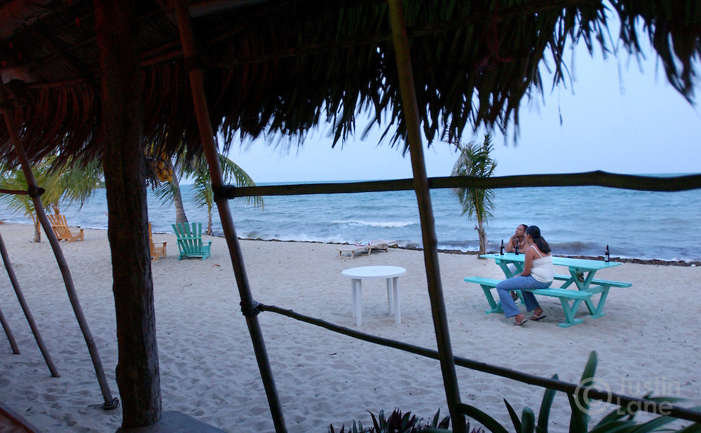 Two young woman have an early evening drink at one of the beach front bars in Placencia, Belize, a beach town in the southern part of the country.<br />JUSTIN LANE FOR THE NEW YORK TIMES