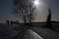 Two men walking in snow covered Kilbogget Park in suburban in Dublin Ireland