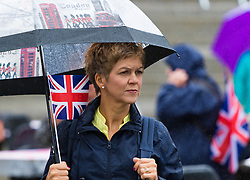 Trafalgar Square, London, June 12th 2016. Rain greets Londoners and visitors to the capital's Trafalgar Square as the Mayor hosts a Patron's Lunch in celebration of The Queen's 90th birthday. PICTURED: A woman watches the performances on stage as the rain continues to fall.