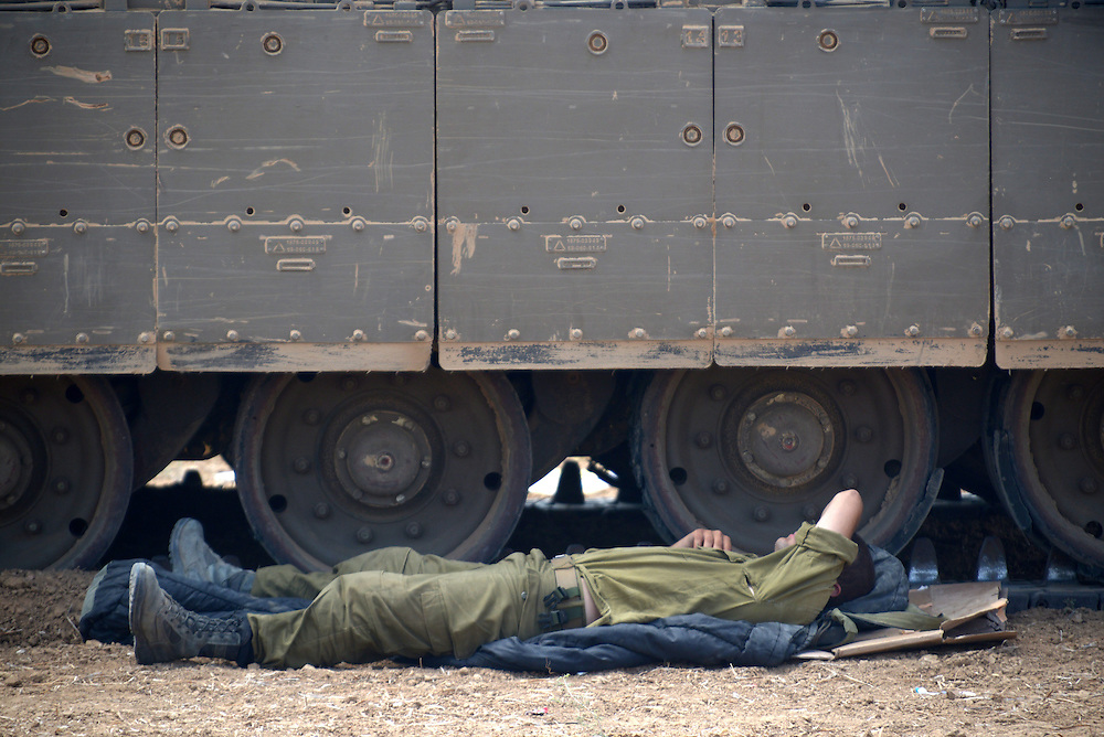 UNSPECIFIED, ISRAEL - JULY 19, 2014: An Israeli soldier sleeps next to an APC in an army deployment area near Israel's border with the Gaza Strip, on July 19, 2014,  on the second day of Israeli ground invasion into Gaza Strip in order to destroy terror tunnels infrastructure. Photo by Gili Yaari