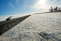 JEROME A. POLLOS/Press..A car travels north Monday on a new section U.S. 95 near Worley surrounded by snow on either side.