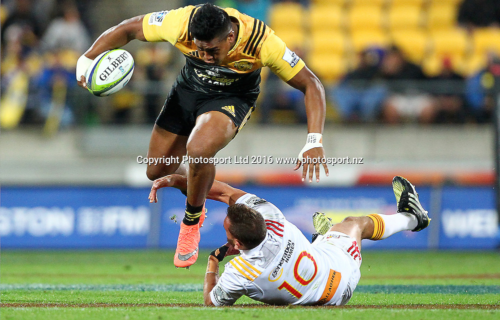 Hurricanes' Julian Savea jumps the tackle of Chiefs' Aaron Cruden during the Round 9 Super Rugby match, Hurricanes v Chiefs at Westpac Stadium, Wellington. 23rd April 2016. Copyright Photo.: Grant Down / www.photosport.nz