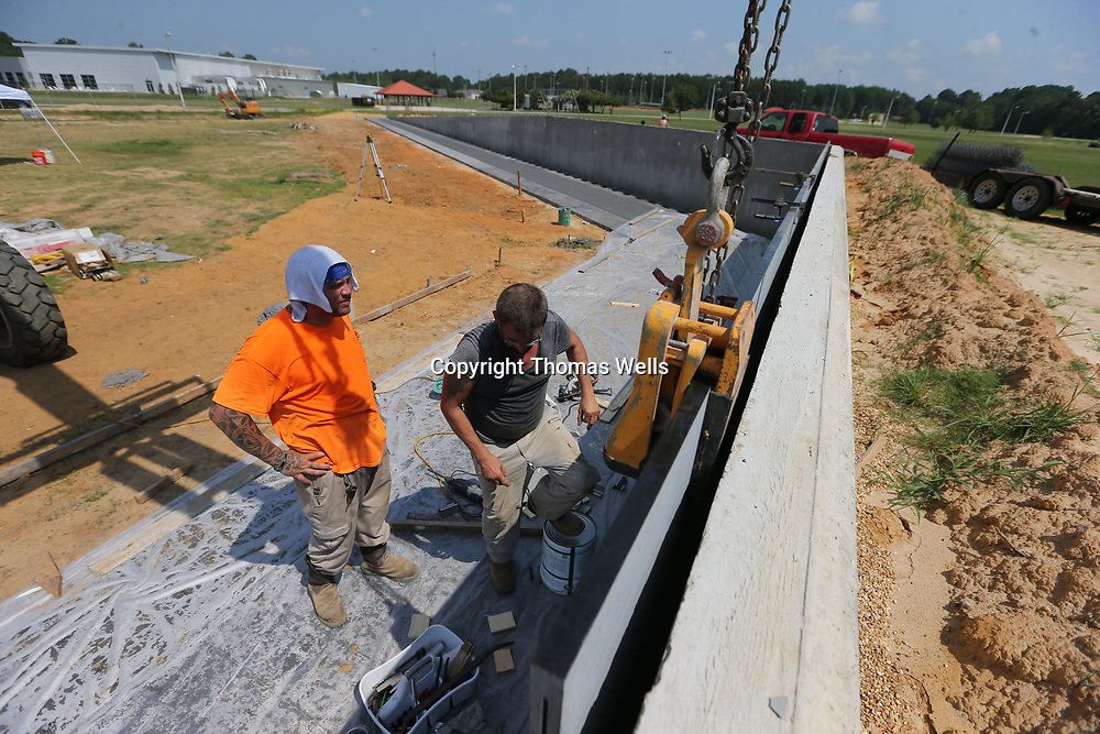 Phillip Taylor, left, and Roger Cole make sure the marble section of the new Vietnam memorial Wall is level and is in the right order before securing it in place. The wall which is a 60% replecia of the original wall is being built at Veterans Park in Tupelo.