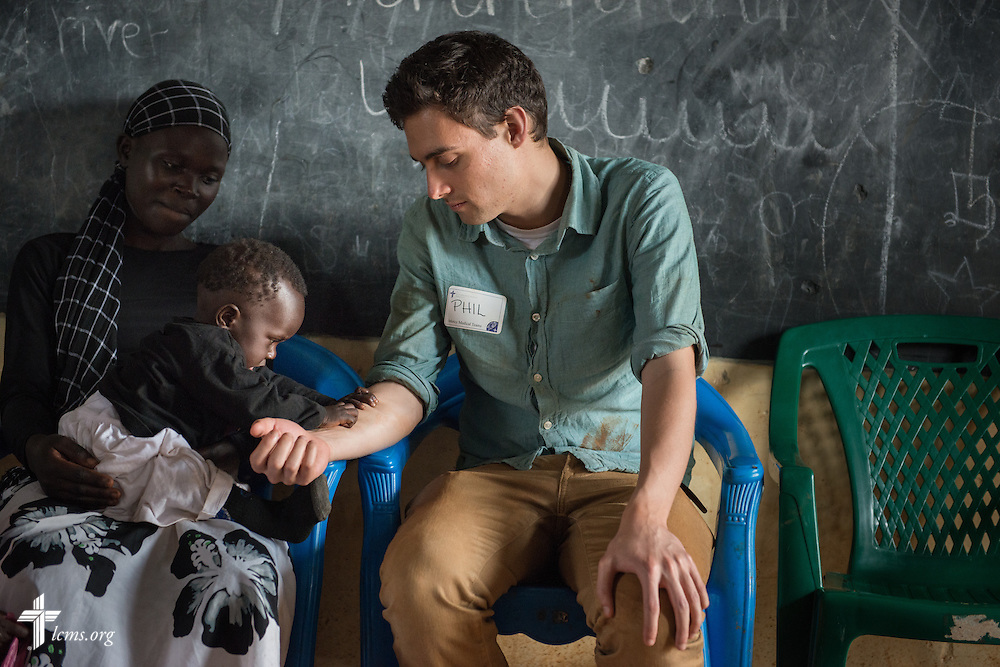 Phil Jaseph, a GEO missionary in Kenya serving as the communications specialist for the Africa region, plays with an infant during a Mercy Medical Team clinic Tuesday, June 10, 2014, at the Luanda Doho Primary School in Kakmega County, Kenya. LCMS Communications/Erik M. Lunsford