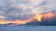 Light from setting sun imparts warm glow to mist rising off of the Susitna River in Talkeetna in Southcentral Alaska. Winter.
