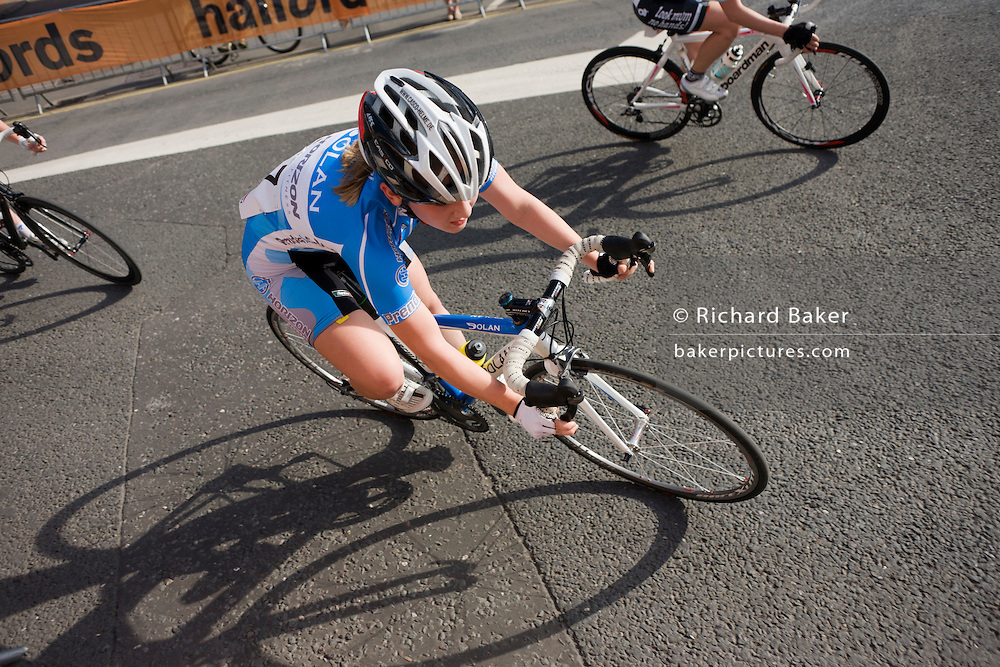 With bike shadows, speeding women cyclists turn into a corner of a Woking street during the Halfords 2011 Tour series.