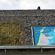 """Nederland Den Oever Zurich 22 november 2008 20081122 Foto: David Rozing ..Serie afsluitdijk. De Afsluitdijk is een belangrijke waterkering en verkeersweg in Nederland. De waterkering sluit het IJsselmeer af van de Waddenzee. Hieraan ontleent de dijk zijn naam. De verkeersweg, onderdeel van Rijksweg a7, verbindt Noord-Holland met Friesland...Informatie plaquette / landkaart van gebied rondom afsluitdijk in de afsluitdijk ter hoogte van de uitkijktoren. Links bronzen beeld Steenzetter.Ter gelegenheid van 50 jaar Afsluitdijk werd in 1982 het beeld de """"Steenzetter"""" van Ineke van Dijk geplaatst. Tekst: """" de strijd tegen het water blijft een strijd door en voor de mens """"  Bezoekers uitkijkpunt, man,  guur weer, wind, koud, capuchon,  deltaplan....Foto David Rozing"""