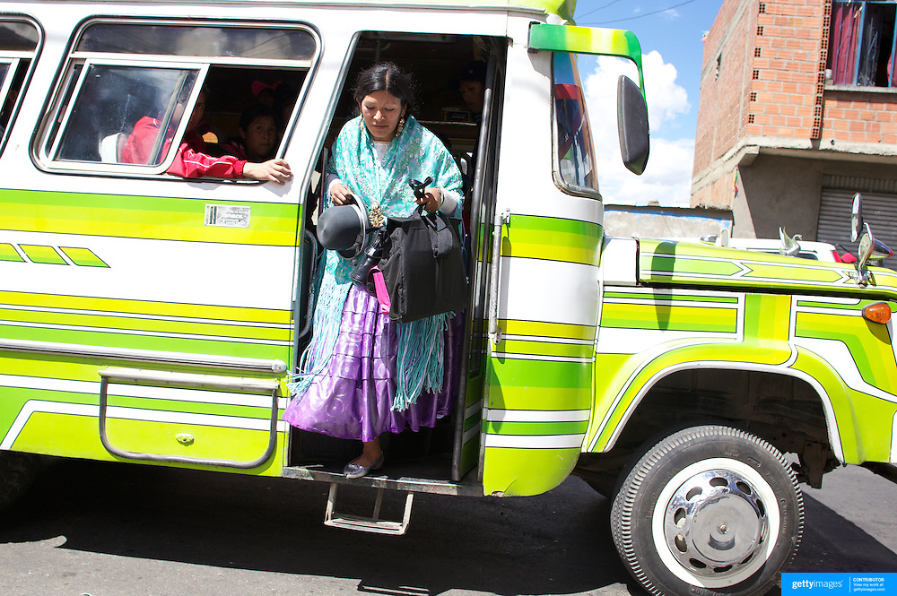 Cholita wrestler Yolanda La Amorosa  gets off the bus with her daughter Adriana near their home in La Paz after collecting her from school. Yolanda is part of the 'Titans of the Ring' wrestling group who perform every  Sunday at El Alto's Multifunctional Centre. Bolivia. The wrestling group includes the fighting Cholitas, a group of Indigenous Female Lucha Libra wrestlers who fight the men as well as each other for just a few dollars appearance money. El Alto, Bolivia, 17th March 2010. Photo Tim Clayton
