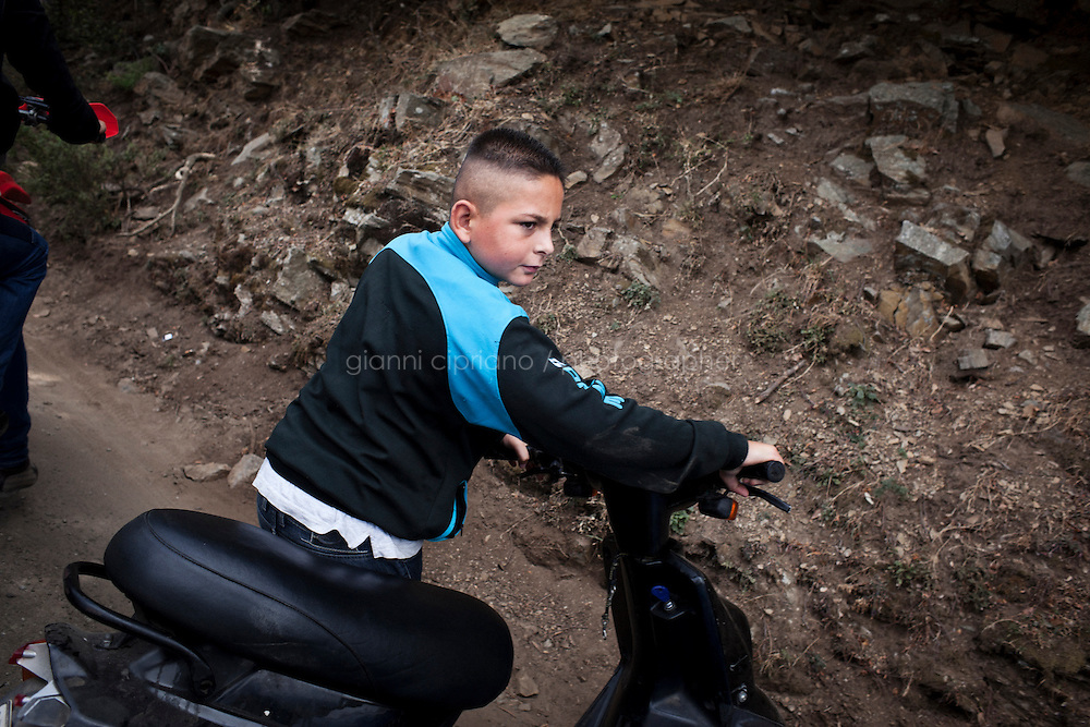 Polsi, Italy - 2 September, 2012: A 12 years old boy makes a U-turn with his scooter on the street that leads to the Sanctuary of Our Lady of Polsi, a mafia stronghold in Calabria, Italy, on September 2nd, 2012. <br /> <br /> The Sanctuary of Our Lady of Polsi, also known as the Sanctuary of Santa Maria di Polsi or Our lady of the Mountain, is a Christian sanctuary in the heart of the Aspromonte mountains, near San Luca in Calabria. The chiefs of the Calabrian criminal consortium, the 'Ndrangheta, have held annual meetings at the Sanctuary. According to the pentito Cesare Polifroni &ndash; a former member turned state witness &ndash; at these meetings, every boss must give account of all the activities carried out during the year and of all the most important facts taking place in his territory such as kidnappings, homicides, etc.<br /> <br /> Calabria is one of the poorest Italian regions which suffers from lack of basic services (hospitals without proper equipment, irregular electricity and water), the product of disparate political interests vying for power. The region is dominated by the 'Ndrangheta (pronounced en-Drang-get-A), which authorities say is the most powerful in Italy because it is the welthiest and best organized.<br /> <br /> The region today has nearly 20 percent unemployment, 40 percent youth unemployment and among the lowest female unemployment and broadband Internet levels in Italy. Business suffer since poor infrastructure drives up transport costs.<br /> <br /> Last summer the European Union's anti-fraud office demanded that Italy redirect 380 million euros in structural funding away from the A3 Salerno - Reggio Calabria highway after finding widespread evidence of corruption in the bidding processes.