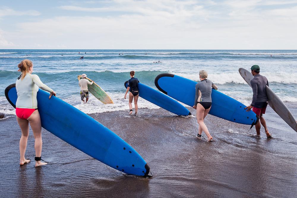 Surfers carry their surfboards at Batubolong beach in Canggu.