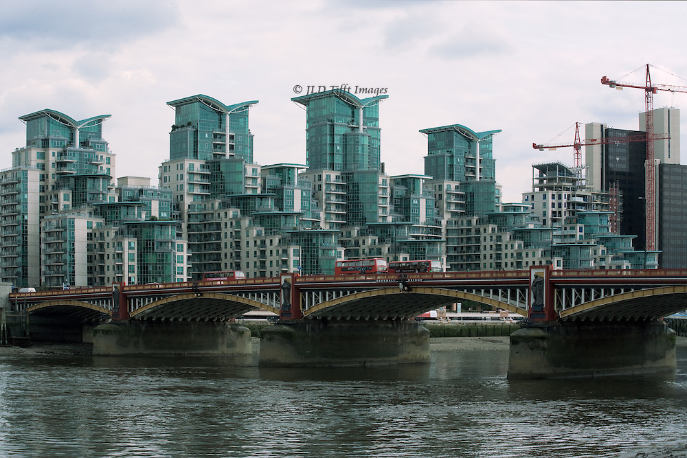 St. George's Wharf development near Vauxhall Bridge: view over the bridge to the high rise apartments, construction cranes beyond.  The four tallest roofs have angular profiles shaped like diagrammatic wings, or opened books.