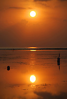 The fiery orb of the sun just after sunrise, reflected in the shallows in Sanur, Bali, Indonesia.