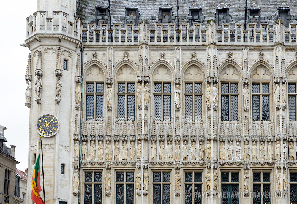 Detail of the front exterior of the Town Hall (Hotel de Ville) in the Grand Place, Brussels. Originally the city's central market place, the Grand-Place is now a UNESCO World Heritage site. Ornate buildings line the square, including guildhalls, the Brussels Town Hall, and the Breadhouse, and seven cobbelstone streets feed into it.