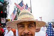 10 APRIL 2006 - PHOENIX, AZ: A man wearing American flags stuck into his hat during an immigration protest in Phoenix, AZ. More than 125,000 people participated in a march for immigrants's rights in Phoenix Monday. The march was a part of a national day of action on behalf of undocumented immigrants. There were more than 100 such demonstrations across the US Monday.  Photo by Jack Kurtz