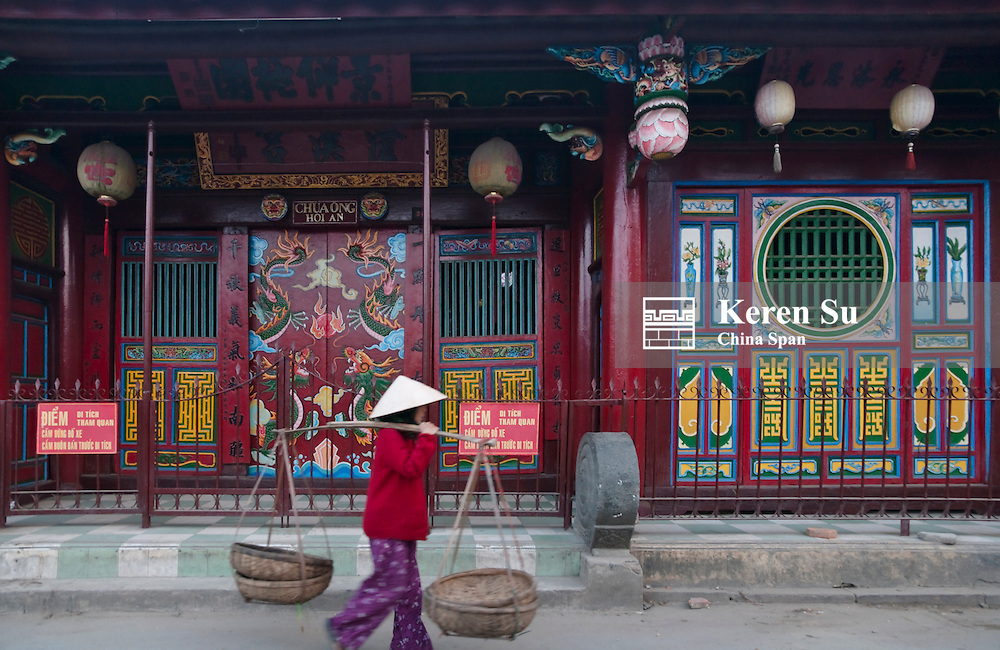 Woman with conical hat outside Chinese temple in Hoi An Ancient Town, UNESCO World Heritage site.