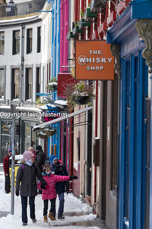View of shops on  historic Victoria Street in Edinburgh Old Town after heavy snow, Scotland, United Kingdom