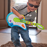 young boy rocking out on his play guitar on his 2nd birthday