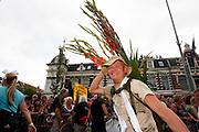 Met gladiolen op zijn rug loopt een wandelaar van de Nijmeegse Vierdaagse op de laatste dag over de Via Gladiola, zoals de Sint Annastraat is omgedoopt tijdens het wandelevenement.