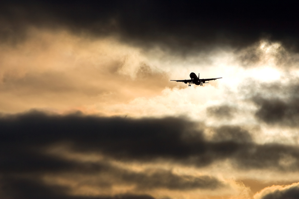 A jet plane coming in for a landing at Chicago's O'Hare International Airport under stormy skies at sunset.