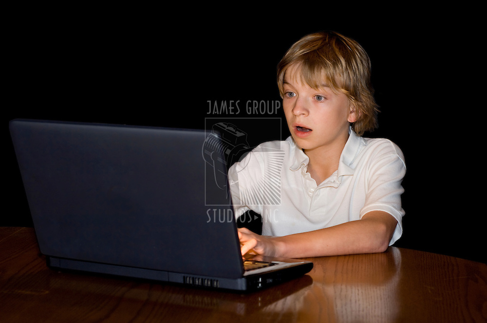 Preteen boy with a mezmerized expression, staring into a computer screen